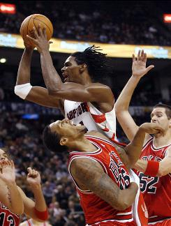 Toronto Raptors forward Chris Bosh goes to the basket against Chicago Bulls defenders James Johnson (L) and Brad Miller during the first half of their game in Toronto Nov. 11. The Raptors won 99-89