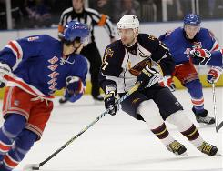 Atlanta Thrashers left wing Ilya Kovalchuk, center, looks to pass during the third period of his team's game Thursday against the Rangers in New York. Ilya Kovalchuk had a goal and two assists in his first game back from a foot injury as the Thrashers won the game 5-3.