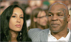 Former heavyweight champion Mike Tyson with his wife Lakiha Spicer in Los Angeles at a boxing match in September. Police are investigating an alleged scuffle Wednesday between Tyson and a photographer at the Los Angeles airport.