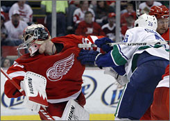 Vancouver's Mikael Samuelsson, a former Red Wing, brushes by Detroit goalie Jimmy Howard in the second period.