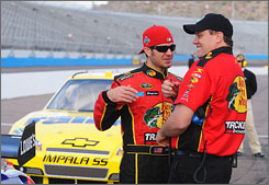 Martin Truex Jr., left, talks with crew chief Kevin Manion during qualifying at Phoenix International Raceway. Truex qualified first, claiming his fourth career pole.