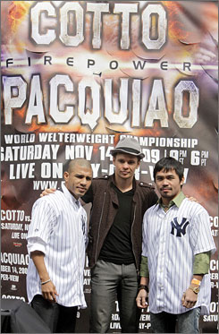 Boxers Manny Pacquiao (right) and Miguel Cotto (left) flank light middleweight boxer Yuri Foreman during a news conference Thursday at Yankee Stadium to promote their bouts.