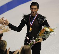 Evan Lysacek takes a lap after the victory ceremony Saturday at Skate America.