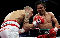 Manny Pacquiao throws a right to the body of Miguel Cotto during their WBO welterweight title fight Saturday.