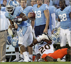 North Carolina's Kendric Burney breaks the tackle of Miami's Damien Berry after one of his three interceptions.