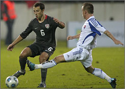 United States player Steve Cherundolo, right, fights for the ball with Slovakia's Miroslav Stoch.