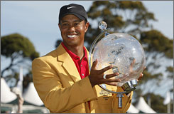 Tiger Woods, wearing the champion's gold jacket, displays his trophy after winning the Australian Masters with a closing round of 4-under 68.