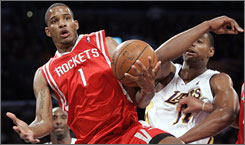 Rockets swingman Trevor Ariza pulls a rebound away from the Lakers' Andrew Bynum during the first half. Ariza left the Lakers in the offseason and struggled in his first game back in Los Angeles, shooting 1-for-10 from the field.