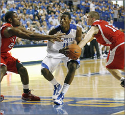 Kentucky guard John Wall drives the lane as Miami (Ohio) forward Nick Winbush, left, and guard Kramer Soderberg defend during the first half. Wall hit a last-second, game-winning jumper to lift the Wildcats to a 72-70 win.