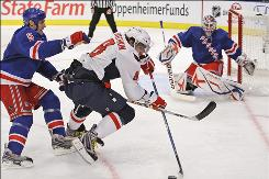 Capitals winger Alexander Ovechkin flies past Rangers defenseman Daniel Girardi as goalie Henrik Lundqvist looks on during the third period. Ovechkin had a goal in the 4-2 win, his first game since Nov. 1.