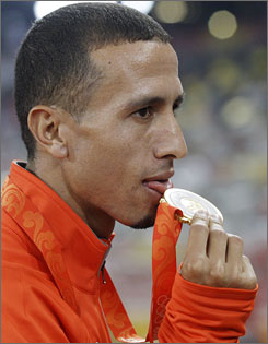 Rashid Ramzi of Bahrain licks the 2008 Olympic gold medal that the International Olympic Committee has stripped from him due to doping.