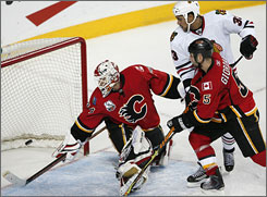 Flames goalie Miikka Kiprusoff watches the puck fall into the net for the fifth of the Blackhawks' five second-period goals during Chicago's rout of Calgary.