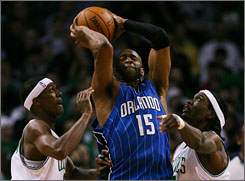 Magic forward Vince Carter protects the ball from a double team by the Celtics' Rajon Rondo and Marquis Daniels.