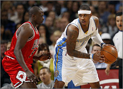 Nuggets forward Carmelo Anthony, right, looks to pass the ball against Bulls forward Luol Deng.