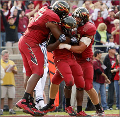 Florida State running back Lonnie Pryor, middle, is mobbed by teammates after scoring the game-winning touchdown in the final minute.
