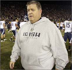 Notre Dame coach Charlie Weis walks of the field after the Irish lost to Connecticut in double overtime.