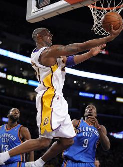 Los Angeles Lakers guard Kobe Bryant puts up a shot as Oklahoma City Thunder guard James Harden, left, and center Serge Ibaka defend during the first half of their game Sunday in Los Angeles. Bryant and the Lakers won 101-85.