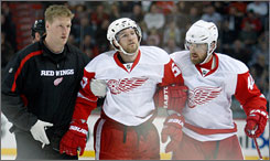 Detroit's Niklas Kronwall, center, is helped off the ice Saturday after a knee-on-knee hit from Montreal's Georges Laraque.