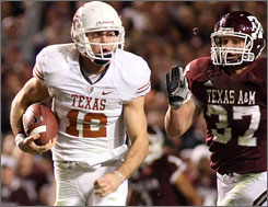 Texas quarterback Colt McCoy eludes Texas A&M's Michael Hodges en route to a rushing touchdown in the first half. McCoy also threw four scores to lead the Longhorns to a 49-39 win.