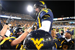 West Virginia teammates lift kicker Tyler Bitancurt after his game-winning field goal that beat No. 9 Pittsburgh as time expired.