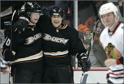 Anaheim's Corey Perry, left, and Teemu Selanne celebrate a Selanne goal as Chicago's John Madden skates by. Selanne scored twice as the Ducks ended the Blackhawks' eight-game winning streak.