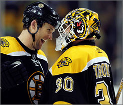 The Bruins' Dennis Wideman and Tim Thomas celebrate beating the Senators to take first place in the Northeast Division.