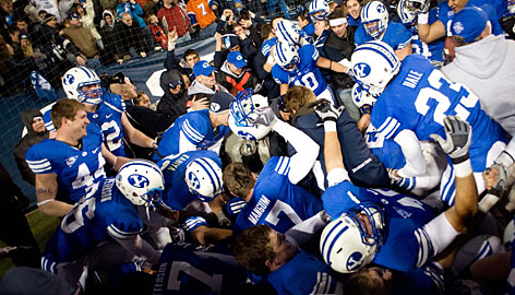 Brigham Young players pile up on Andrew George after his game-winning touchdown catch against Utah in overtime.