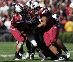 A group of South Carolina defenders swallow Clemson running back C.J. Spiller during the second quarter.