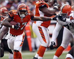The Bengals' Larry Johnson breaks through the line of scrimmage during a run in the first half of Cincinnati's 16-7 victory over Cleveland Sunday.