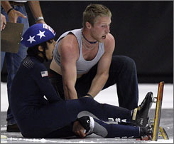 J.R. Celski yells as skater Walter Rusk applies pressure to his knee after Celski cut it with his skate in a crash Sept. 12 in the U.S. Olympic speedskating trials.