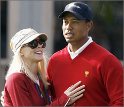 Tiger Woods and wife Elin Nordegren at the Presidents Cup in San Francisco in early October. Woods has withdrawn from the Chevron World Challenge, citing injuries suffered during a car crash last Friday.