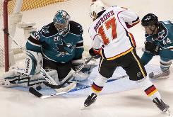 San Jose Sharks goalie Evgeni Nabokov and Marc-Edouard Vlasic stop a shot by the Calgary Flames' Rene Bourque in the third period of their game in San Jose, Calif. The Flames beat the Sharks 2-1.