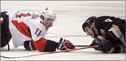 Senators captain Daniel Alfredsson, left, tries to get his stick out from underneath Ducks defenseman  Nick Boynton.