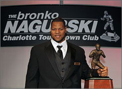 Nebraska defensive tackle Ndamukong Suh displays the Bronko Nagurski Trophy, awarded to the NCAA's top defensive college football player, during a news conference in Charlotte.