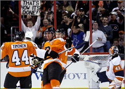 Flyers players celebrate Mike Richards', center, goal on Islanders goalie Martin Biron during the first period. Richards, Jeff Carter and Claude Giroux each scored two goals in Philadelphia's 6-2 victory.