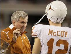 Texas coach Mack Brown, left, talking with Longhorns quarterback Colt McCoy, will become the first college football coach to be paid at least $5 million next season.