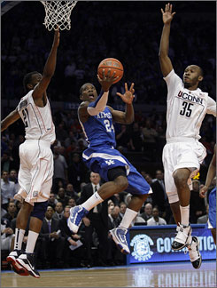 Kentucky's Eric Bledsoe scores on a reverse layup against Connecticut's Stanley Robinson, left, and Charles Okwandu during the first half.