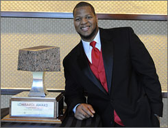 Nebraska's Ndamukong Suh poses with the Lombardi Trophy he won Wednesday as the nation's top lineman. Two days earlier, Suh also won the Bronko Nagurski Trophy given to the top defensive college football player.
