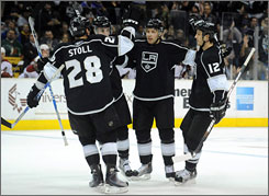 The Kings' Jarret Stoll and Randy Jones (12) congratulate teammate Jack Johnson after a first-period goal as Los Angeles snapped the Coyotes' five-game winning streak.