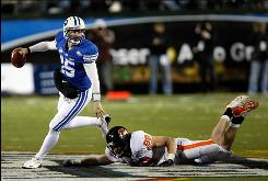 BYU quarterback Max Hall escapes the rush of Oregon State defensive end Gabe Miller during the Las Vegas Bowl at Sam Boyd Stadium on Tuesday. No. 14 BYU defeated No. 20 Oregon State 44-20.