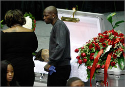 Bengals receiver Chad Ochocinco pays his respects at the casket of late teammate Chris Henry on Tuesday.