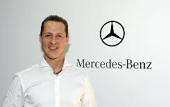 Formula One world champion Michael Schumacher poses in front of the Mercedes-Benz logo at the team's headquarters in Brackley, England.