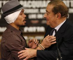 Promoter Bob Arum, right, welcomes Manny Pacquiao to a postfight press conference following Pacquiao's Nov. 14 win over Miguel Cotto.