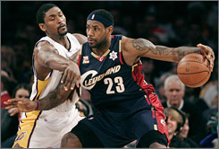 The Cavaliers' LeBron James, right, backs down the Lakers' Ron Artest in the paint during the first quarter. James had 26 points and nine assists as Cleveland rolled to a 102-87 win.