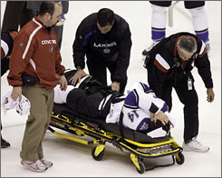 Kings right winger Justin Williams is wheeled off the ice by medical personnel after injuring his right leg early in the first period. Coyotes defenseman Ed Jovanovski and Kings center Anze Kopitar had fallen on top of Williams as his knee buckled beneath him.