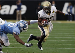 Pittsburgh's Dion Lewis races past North Carolina's Zach Brown during the first half. Lewis rushed for 159 yards and a touchdown in the Panthers' 19-17 win.