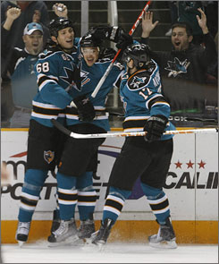 Sharks right wing Devin Setoguchi, center, celebrates with teammates Frazer McLaren, left, and Torrey Mitchell after scoring against the Coyotes during the first period.