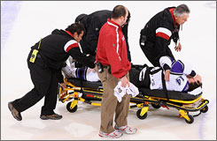 Los Angeles Kings winger Justin Williams is taken off the ice on a stretcher Saturday after two players fell onto him.