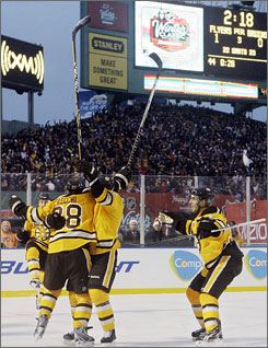 Bruins teammates congratulate Mark Recchi as the Fenway Park scoreboard marks the time of his tying goal.