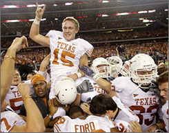 Texas kicker Hunter Lawrence is carried off the field after he booted the game-winning field goal in Texas' victory over Nebraska in the Big 12 title game.